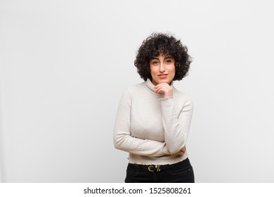 young pretty afro woman looking happy and smiling with hand on chin, wondering or asking a question, comparing options
