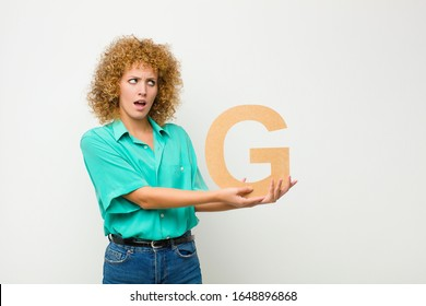 young pretty afro woman surprised, shocked, amazed, holding the letter G of the alphabet to form a word or a sentence.