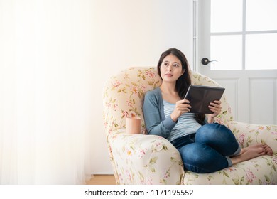 young pretty aisan girl chilling at home and sitting on a cozy sofa in the living room while using tablet.