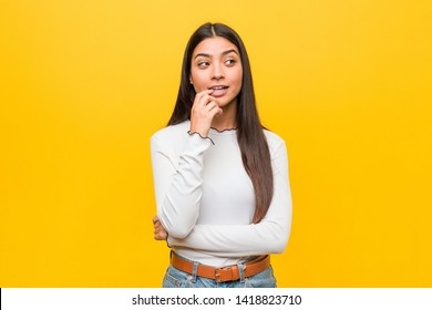 Young pretty arab woman against a yellow background relaxed thinking about something looking at a copy space.