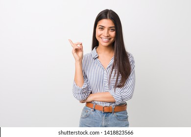 Young pretty arab woman smiling cheerfully pointing with forefinger away.