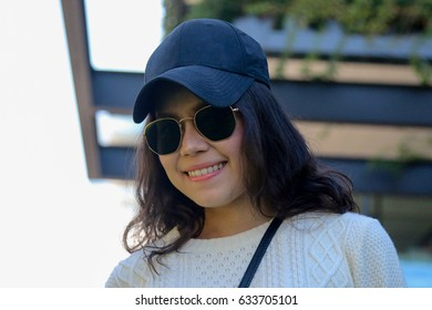 Young pretty Asia girl posting on the street at sunny day, having fun alone, stylish casual clothes with bag ,hat and sunglasses,travel concept.
