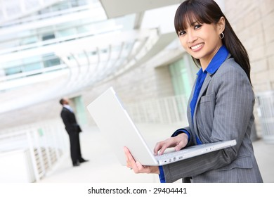 A young pretty asian business woman on laptop computer at work