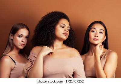 young pretty asian, caucasian, afro woman posing cheerful together on brown background, lifestyle diverse nationality people concept