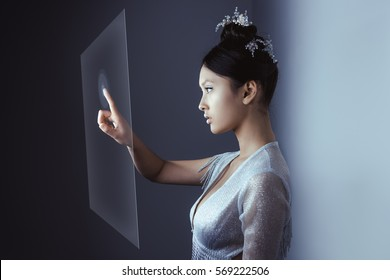 Young pretty asian female touching digital hologram screen. Future woman concept art. Fashion futuristic young attractive multi-racial Asian Caucasian model with futuristic make-up indoors. Copy space