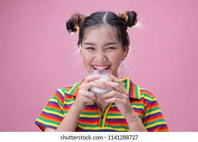Young pretty asian girl drinking milk on pink background