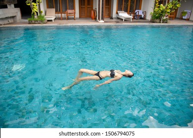 Young and pretty Asian girl friend who is wearing a bikini and enjoying a backstroke in the resort pool.