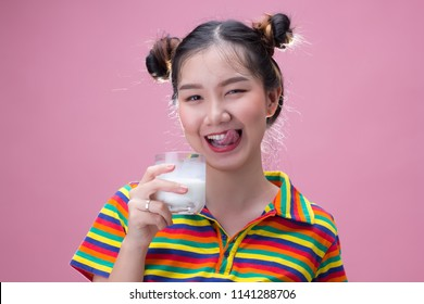 Young pretty asian girl holding a glass of milk on pink background