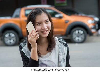a young pretty Asian girl using mobile phone