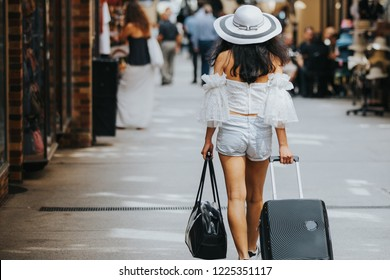 Young pretty Asian lady browsing around the city .Her hand is holing luggage and carry on bag with the nice fashion outfit