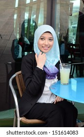 young pretty Asian muslim business woman in head scarf at cafe