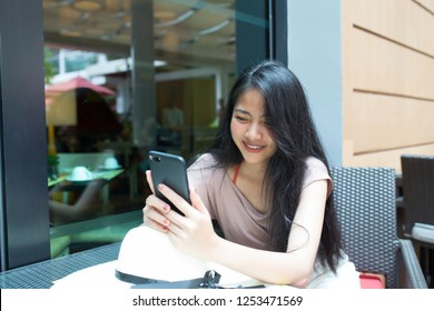 Young pretty asian woman enjoy with smart phone in coffee shop