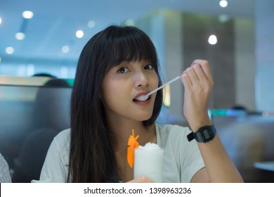 Young pretty asian woman enjoy with fresh coconut water frappe in the restaurant