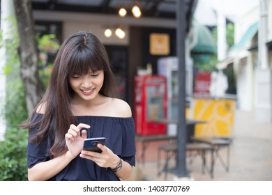 Young pretty asian woman enjoy with her smart phone