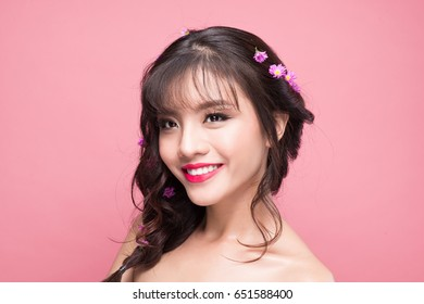Young pretty asian woman with flowers on hair close up on pink background
