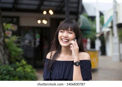 Young pretty asian woman happy talking on smartphone in the city