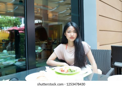 Young pretty asian woman having meal in the restaurant