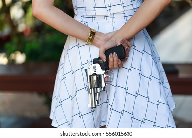 Young pretty Asian woman hiding a hand gun behind her back with