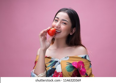 Young pretty asian woman holding a ripe tomato with happiness