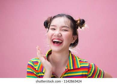 Young pretty asian woman laugh with happiness on pink background