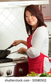 Young Pretty Asian Woman Preparing  Food in Kitchen