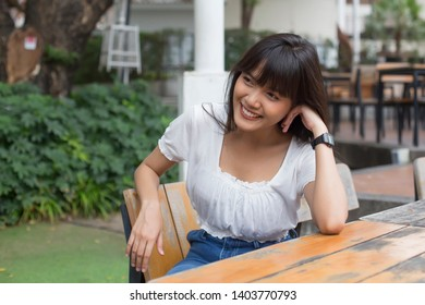 Young pretty asian woman sitting in outdoor restaurant, smiling and relax