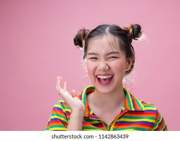 Young pretty asian woman smiling with happiness on pink background