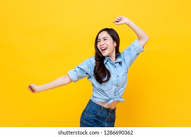 Young pretty Asian woman smiling with energetic movement studio shot isolatede on colorful yellow background