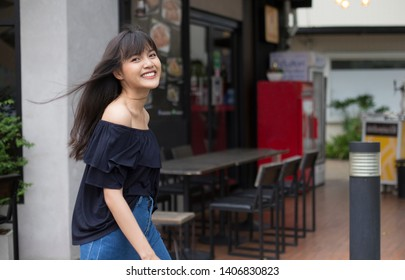 Young pretty asian woman walking with happy on restaurant background