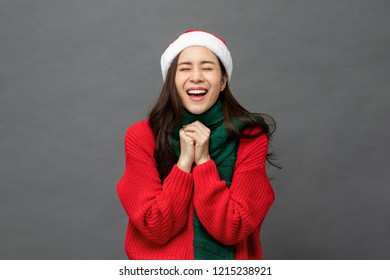Young pretty Asian woman wearing red Christmas sweater and hat in surprised excited emotion