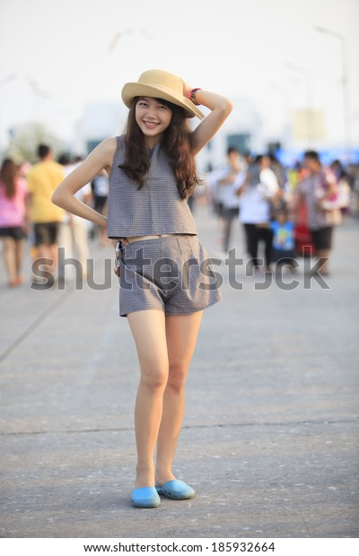 young and pretty asian woman wearing straw hat standing and posting with crowded behind