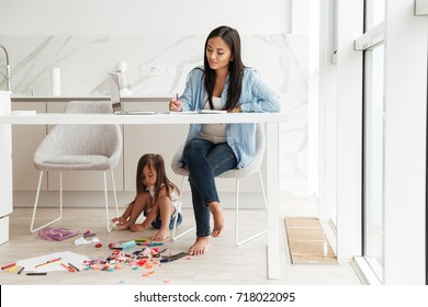 Young pretty asian woman working with laptop and notepad while her little daughter playing on a floor at the kitchen