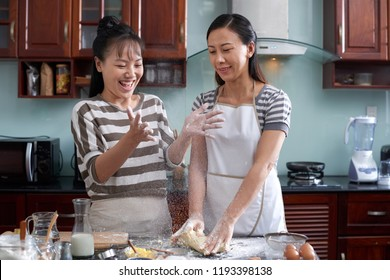Young pretty Asian women kneading cookie dough in home kitchen, dusting hands with flour and smiling cheerfully