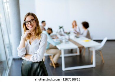 Young pretty attractive female manager standing in modern office
