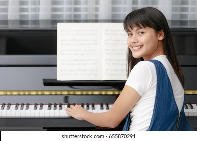 Young pretty beautiful Asian girl smiling  sitting at piano with blur music sheet and looking to camera