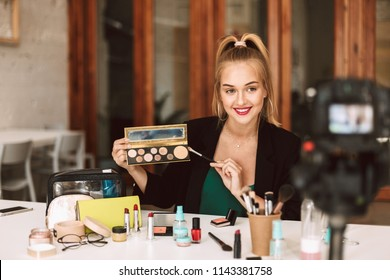 Young pretty beauty blogger talking about cosmetic products recording new video for vlog