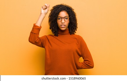 young pretty black woman feeling serious, strong and rebellious, raising fist up, protesting or fighting for revolution against orange wall
