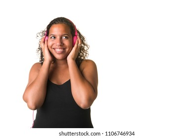 Young pretty black woman listening to music on a pink headphone isolated on a white background
