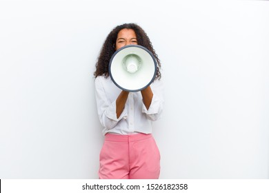 young pretty black woman with a megaphone against white wall