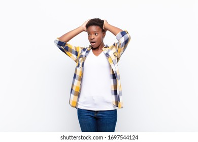 young pretty black womanwith open mouth, looking horrified and shocked because of a terrible mistake, raising hands to head