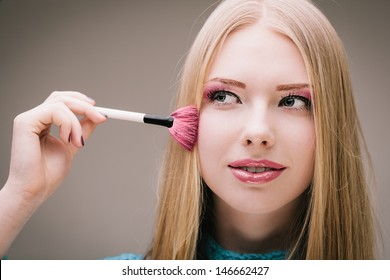 Young pretty blond girl doing makeup
