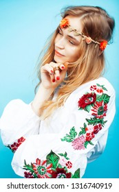 young pretty blond girl posing on blue background, fashion style hippie boho flowers on head