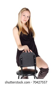 young pretty blond girl standing near the chair