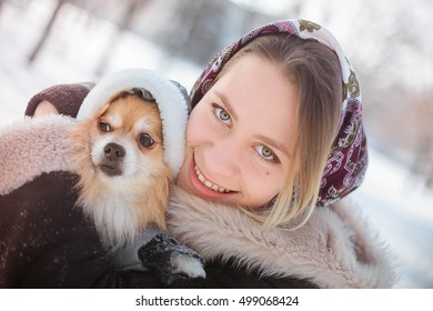 Young pretty blond girl in a winter snowy park walks her Pomeranian in a gray suit