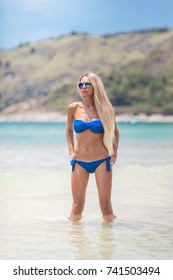 Young pretty blond woman in blue bikini on a white tropic beach