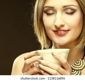young pretty blond woman drinking coffee over beige background