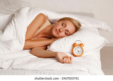 Young pretty blond woman in her bed feeling sleepy with orange alarm clock near her head