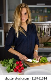 Young pretty blond woman making salad in kitchen