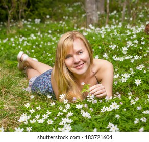 Young pretty blond woman on a meadow with flowers
