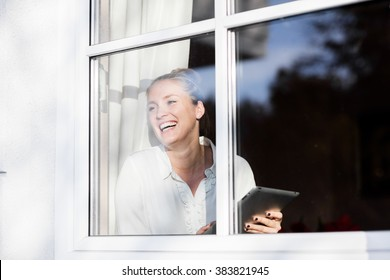 Young pretty blond woman sitting at the window with her tablet and relaxing in the sun